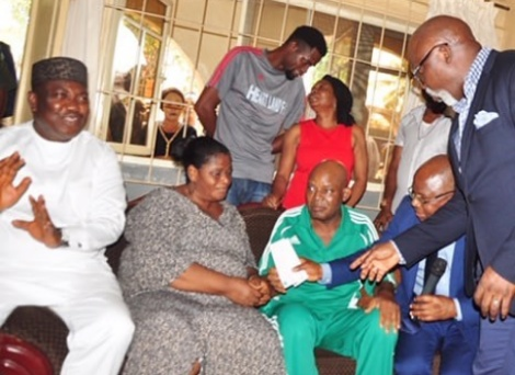 Femi Otedola presents a cheque to Chukwu for his medical bill