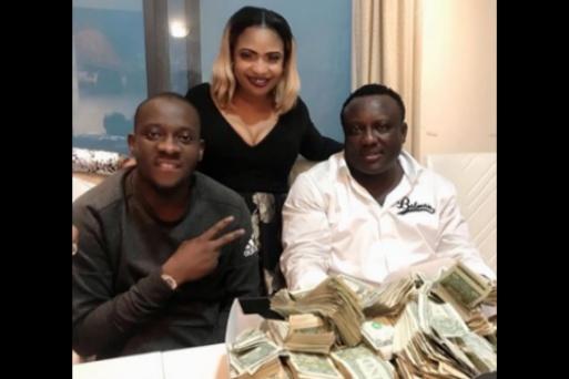 Laide Bakare poses with wads of $1 bills, alongside Saheed Osupa